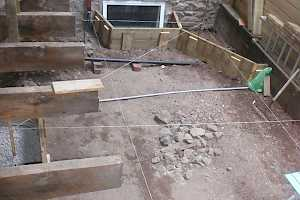 The area to the side of the house was dug down to bedrock and levelled, taking care to allow for window spaces and a planing area.