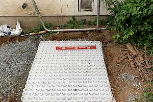 Pl.ace and level the foundation grid. Note the membrane attached to the foundation grid which serves as a weed suppresent.